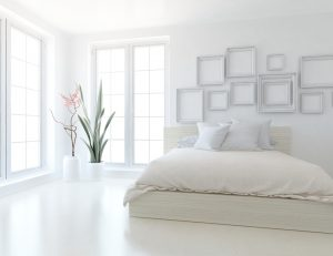 White,Minimalist,Bedroom,Interior,With,Double,Bed,On,A,Wooden